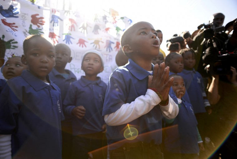A student chants a prayer as his class visits Medi-Clinic Heart Hospital to pay respect where ailing former South African President Nelson Mandela is being treated in Pretoria. (Dylan Martinez/Reuters)