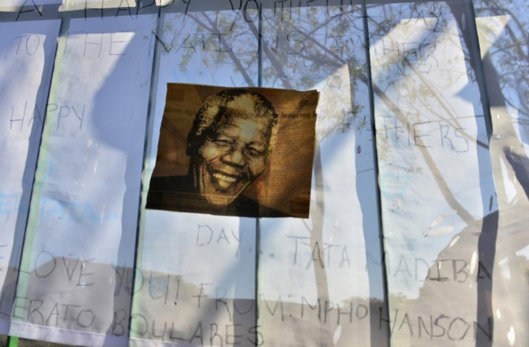 A poster of Mandela is seen on get well messages outside a Pretoria hospital where former South African President Nelson Mandela is being treated , June 25, 2013. Mandela remains in a critical condition in hospital, the government said on Tuesday. (Mujahid Safodien /Reuters)