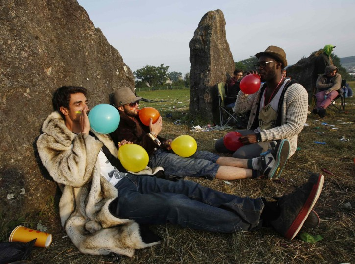 Festival goers inhale laughing gas at sunrise at the stone circle on the second day of Glastonbury music festival at Worthy Farm in Somerset, June 27, 2013. (Olivia Harris/Reuters)