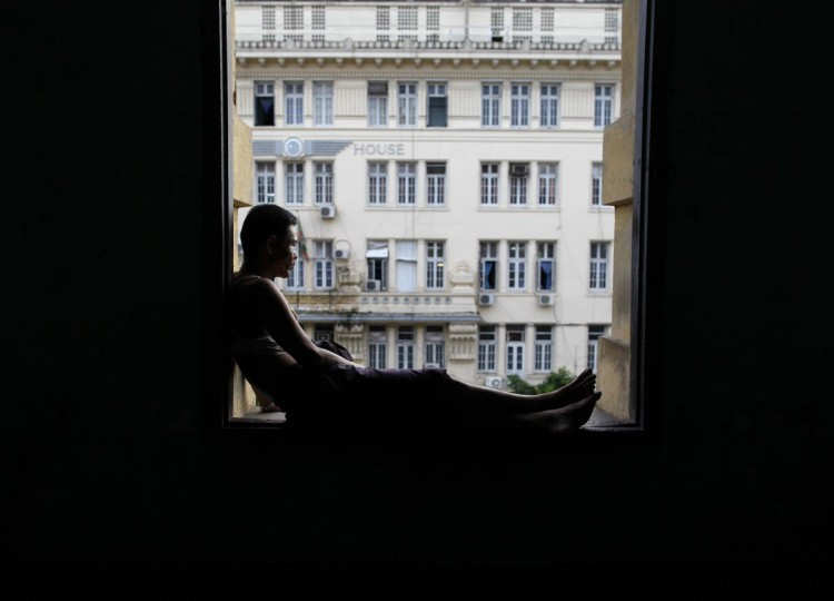 A man sits in a window of a colonial building in Yangon June 3, 2013. (Soe Zeya Tun/Reuters)