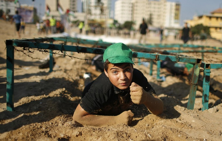 Palestinian boy Mahmoud Haniyeh, 13, crawls during a military-style exercise at a summer camp organized by the Hamas movement in Gaza City. Tens of thousands of children from the Gaza Strip spend at least part of their holidays in special summer camps, arranged around a wide array of activities. Some, organized by the United Nations, offer sports, art and dance classes. Others, laid on by Gaza's Islamist rulers Hamas, include fun and games, while seeking to reinforce religious values and awareness of the conflict with Israel. (Mohammed Salem/Reuters)