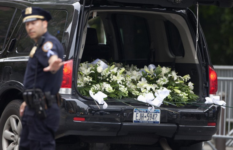 A police officer directs traffic as an SUV full of flowers pulls up to the Cathedral Church of St. John The Divine for the funeral of actor James Gandolfini. (Carlo Allegri/Reuters)