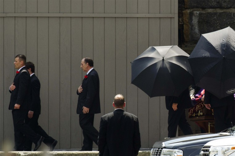 Mourners use umbrellas to block the view of a casket as it is wheeled out of the funeral services of James Gandolfini outside the Cathedral Church of Saint John the Divine in New York. (Lucas Jackson/Reuters)