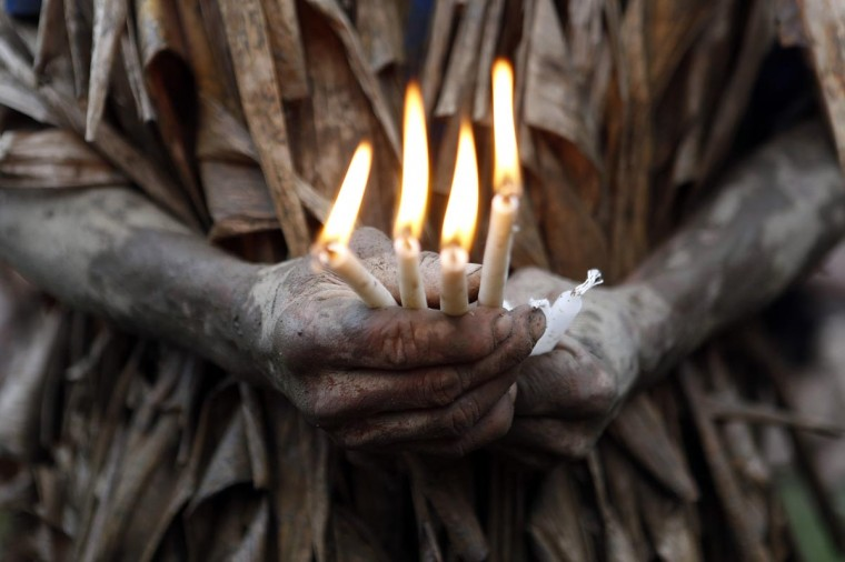 A resident, covered with mud and dried banana leaves, hold candles as he attends a mass celebrating the feast day of the Catholic patron Saint John the Baptist in the village of Bibiclat, Nueva Ecija, north of Manila, June 24, 2013. Hundreds of devotees took part in this annual religious tradition, which has been held in the village since 1945. (Cheryl Ravelo/Reuters)