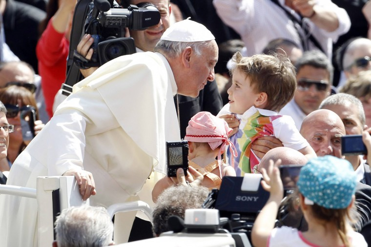 Pope Francis kisses a child as he arrives to lead the weekly audience in Saint Peter's Square at the Vatican. (Giampiero Sposito/Reuters)