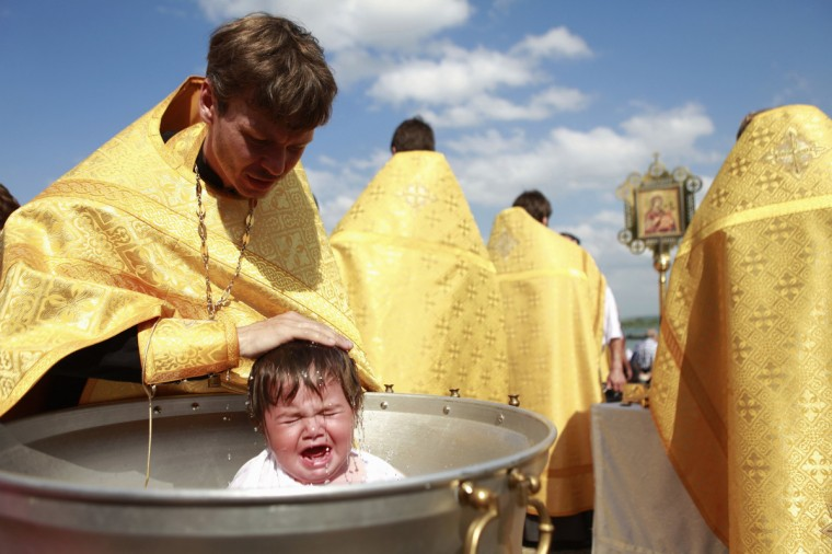 A priest baptises a child at Novopyatigorsk lake near the Russian southern town of Pyatigorsk. About 80 people were baptized by a Russian orthodox church during the ceremony. (Eduard Korniyenko/Reuters photo)