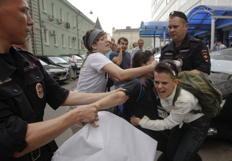 "A radical Orthodox believer (C) crushes an egg on a gay rights activist during a protest against a proposed new law termed by the State Duma as ""against advocating the rejection of traditional family values"" in central Moscow. Russian police detained more than 20 gay rights activists involved in a ""kissing protest"" on Tuesday outside parliament where lawmakers were preparing to pass a bill banning homosexual ""propaganda"". (Maxim Shemetov/Reuters)"