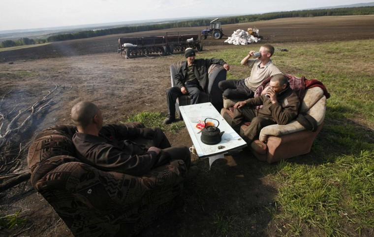 Inmates sit on a sofa and armchairs while having a meal during a work break on an agrarian field of a penal colony settlement, some 25 miles northeast of Russia's Siberian city of Krasnoyarsk, June 6, 2013. Some 250 inmates, who were given life sentences and committed to forced labor works in security prison camps, operate on regional penitentiary system agrarian fields and at farms, according to the regional penitentiary system official representatives. Every hour inmates are obliged to sign a document during working hours as part of a regular controlling check, conducted by prison guards. (Ilya Naymushin/Reuters)