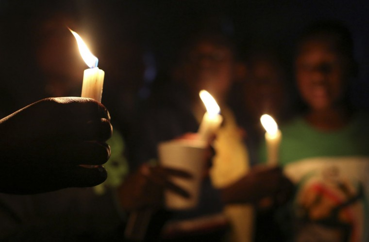 Locals hold candles as they sing for ailing former South African President Nelson Mandela outside the Medi-Clinic Heart Hospital, where he is being treated, in Pretoria, South Africa, June 29, 2013. (Siphiwe Sibeko/Reuters)