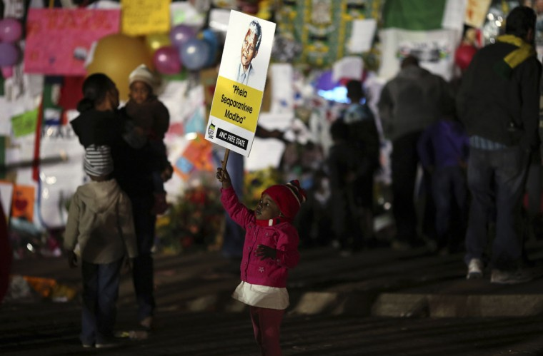 A girl holds a Mandela poster in front of messages of support for ailing former South African President Nelson Mandela outside the Medi-Clinic Heart Hospital, where he is being treated, in Pretoria, South Africa on June 29, 2013. (Siphiwe Sibeko/Reuters)