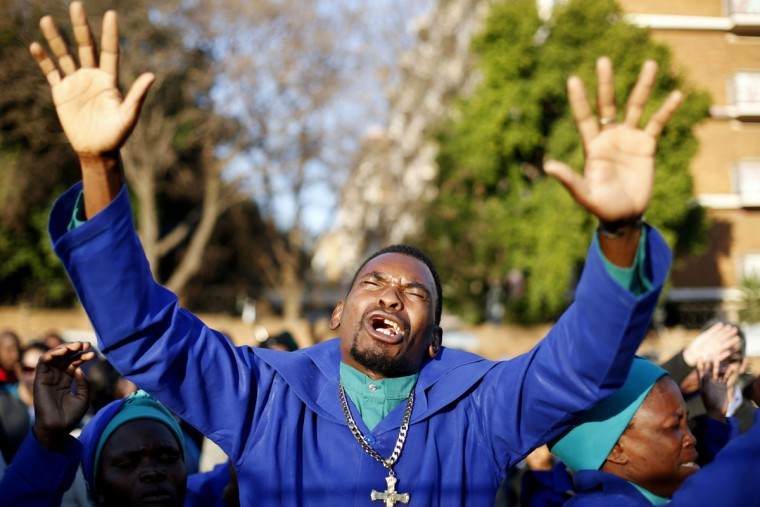 Members of a church group pray for ailing former South African President Nelson Mandela outside the Medi-Clinic Heart Hospital where he is being treated in Pretoria, South Africa, on June 29, 2013. (Kevin Coombs/Reuters)