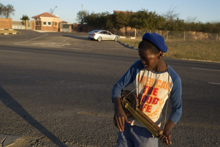 A boy plays a homemade guitar in front of the ailing former South African President Nelson Mandela's home in Qunu, Eastern Cape, South Africa, on June 29, 2013. (Siegfried Modola/Reuters)