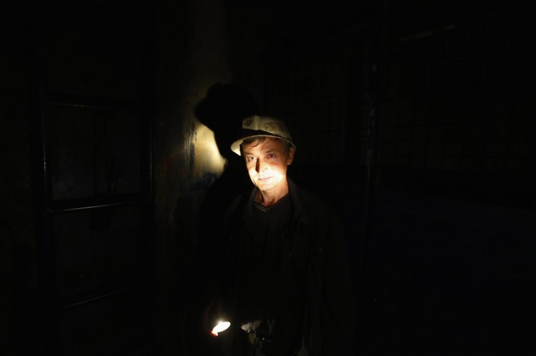 A miner uses a flashlight in an elevator as he descends to the copper mine in the Serbian town of Bor, some 148 miles southeast from Belgrade June 8, 2013. In Serbia, foreign companies are picking up a long tradition of prospecting for gold and copper and discovering deposits that could mark a revival of the country's mining sector. Pressured by cautious investors, international mining companies are putting riskier exploration projects in places like Africa on ice and turning to developments where infrastructure and political risk are lower. (Marko Djurica/Reuters)