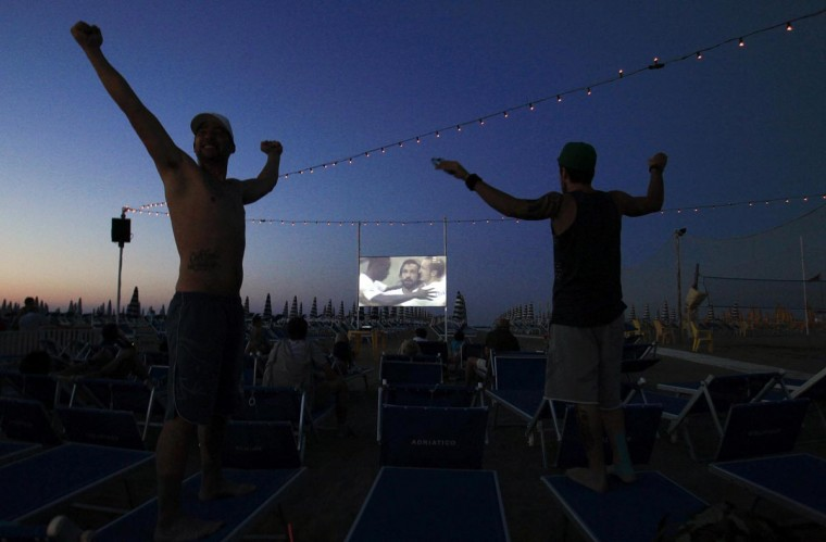 Italian supporters celebrate a goal by Italy's national soccer team player Andrea Pirlo against Mexico, as they watch a broadcast of the Confederations Cup Group A soccer match on a screen at a beach in Cesenatico, on the Adriatic seaside June 16, 2013. (Alessandro Garofalo/Reuters)