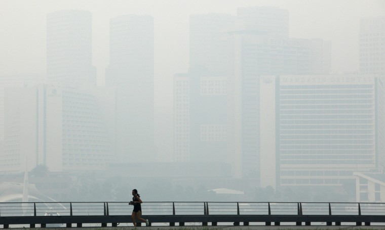 A jogger passes the hazy skyline of Singapore. Singapore's worst air pollution in 16 years sparked diplomatic tension on Tuesday, as the city-state urged Indonesia to provide data on company names and concession maps to enable it to act against plantation firms that allow slash-and-burn farming. (Edgar Su/Reuters photo)