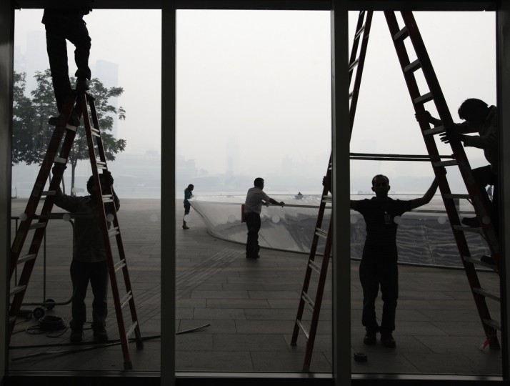 "Construction laborers working at The Shoppes at Marina Bay Sands are pictured against the hazy skyline of Singapore. Singapore's air pollution level rose to ""very unhealthy"" levels late on Wednesday, with the main pollution index hitting the highest on record, as smoke from Indonesian forest fires enveloped the city-state. (Edgar Su/Reuters photo)"