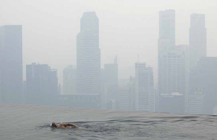 A hotel guest swims in the pool of the Marina Bay Sands Skypark overlooking the haze covered skyline of Singapore June 17, 2013. The haze worsened on Monday with the Pollutant Standards Index (PSI) hitting 105 at 3pm according to local media. (Edgar Su/Reuters)