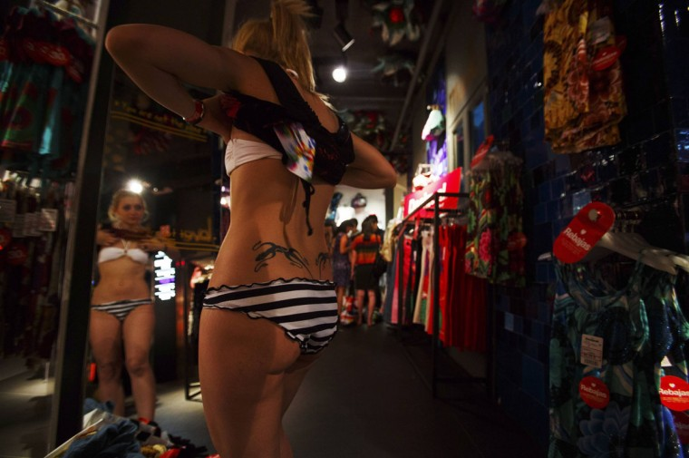 A woman in her underwear tries on clothes inside a clothing store in Madrid, Spain. A Spanish retail clothing chain said they would give clothes to people who came in their underwear as part of a promotional publicity stunt. (Sergio Perez/Reuters)