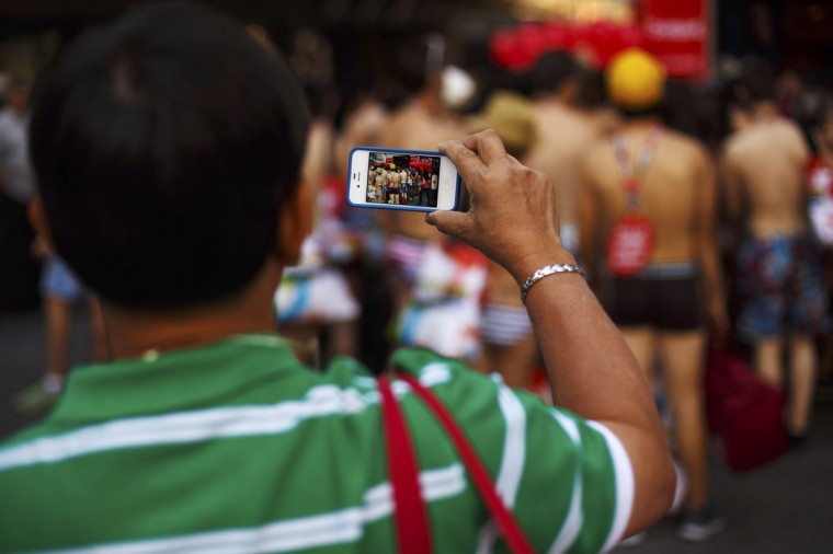 A tourist records a video of people in their underwear with his mobile phone before they enter a clothing store in Madrid, Spain. A Spanish retail clothing chain said they would give clothes to people who came in their underwear as part of a promotional publicity stunt. (Sergio Perez/Reuters)