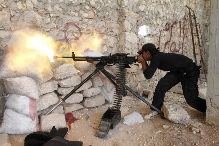 A Free Syrian Army fighter shoots his weapon near Kindi hospital, which is under the control of forces loyal to President Bashar Al-Assad, as both sides fight to take control of the hospital in Aleppo. (Hamid Khatib/Reuters)