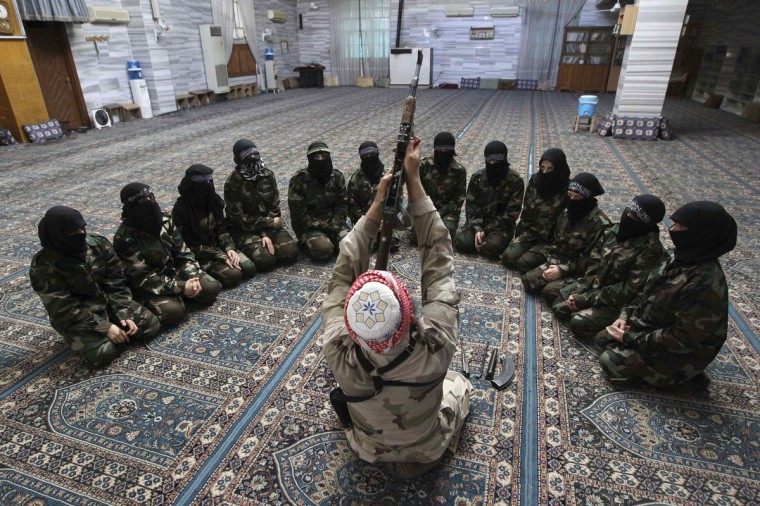 Abu al-Taib, the leader of Ahbab Al-Mustafa Battalion, demonstrates to female members as he holds a gun during a military training in a mosque in the Seif El Dawla neighbourhood in Aleppo. (Muzaffar Salman/Reuters)