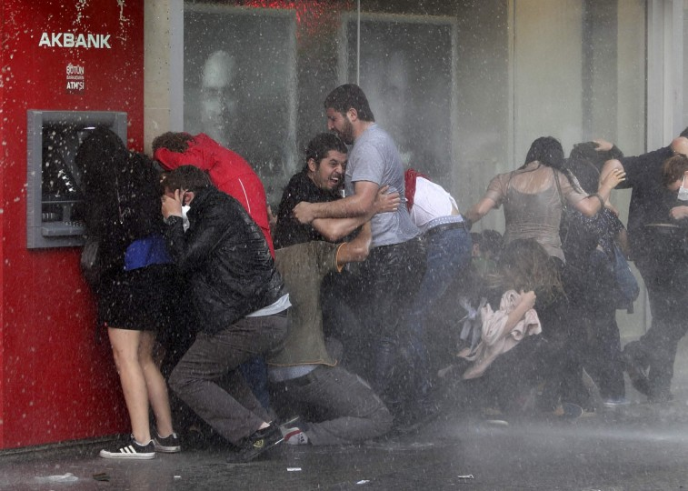 Anti-government protesters try to protect themselves from a water cannon as riot police disperse them during a protest in Ankara. Turkish demonstrators demanded the sacking of police chiefs on Wednesday over a fierce crackdown on days of unprecedented protest against what they see as Prime Minister Tayyip Erdogan's authoritarian rule. (Umit Bektas/Reuters)