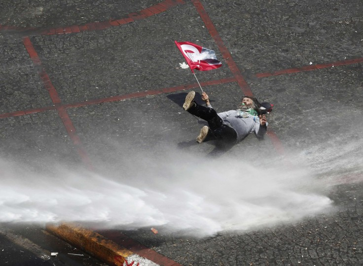 A protester holding a flag bearing an image of Mustafa Kemal Ataturk, founder of modern Turkey, falls as he is hit by a jet of water from a police water cannon during clashes in Istanbul's Taksim Square. (Osman Orsal/Reuters)