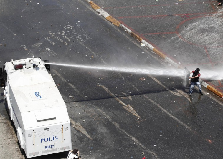 A protester holding a shield attempts to block a jet of water from a police water cannon during clashes in Istanbul's Taksim Square. (Osman Orsal/Reuters)