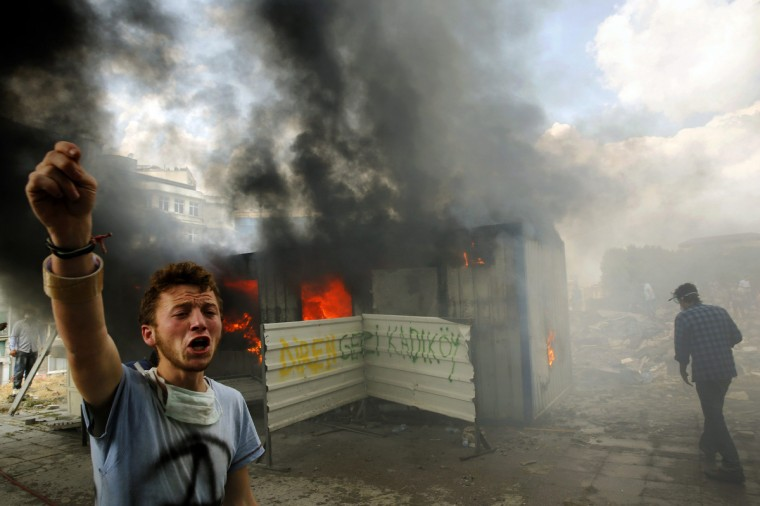 An anti-government protester shouts for help to extinguish a burning container in Istanbul's Taksim square. It was not clear why the container was on fire. Pockets of protesters clashed with Turkish riot police overnight and a union federation began a two-day strike on Tuesday as anti-government demonstrations in which two people have died stretched into a fifth day. (Yannis Behrakis/Reuters)