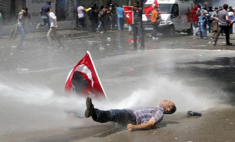 A man is hit by a jet of water as riot police use a water cannon to disperse demonstrators during a protest against Turkey's Prime Minister Tayyip Erdogan and his ruling Justice and Development Party (AKP) in central Ankara June 1, 2013. (Umit Bekta/Reuters)