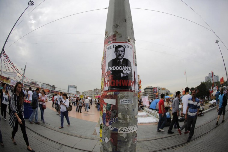"""People walk past a poster depicting Turkish Prime Minister Tayyip Erdogan, put up by demonstrators, at Taksim Square in Istanbul June 7, 2013. Erdogan flew back to a Turkey rocked by days of anti-government unrest on Friday and declared before a sea of flag-waving supporters at Istanbul airport: """"These protests must end immediately."""" """"No power but Allah can stop Turkey's rise,"""" he told thousands who gathered in the early hours to greet him in the first pro-Erdogan rally since demonstrations began a week ago. Picture taken with a fish-eye lens. (Murad Sezer/Reuters)"""