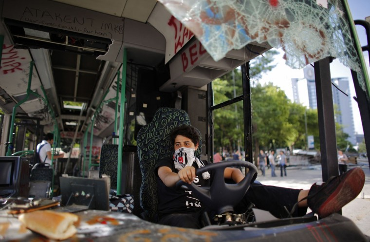 """A Besiktas soccer fan uses his team's scarf as a mask while sitting in a damaged bus at Taksim Square in central Istanbul June 4, 2013. Days of anti-government protest in Turkey have achieved one feat that has eluded the authorities for years: uniting the fiercely rival and sometimes violent supporters of Istanbul's """"Big Three"""" football clubs. Besiktas, Galatasaray and Fenerbahce fans have come together in newfound solidarity during five days of demonstrations against Prime Minister Tayyip Erdogan's government. (Murad Sezer/Reuters)"""