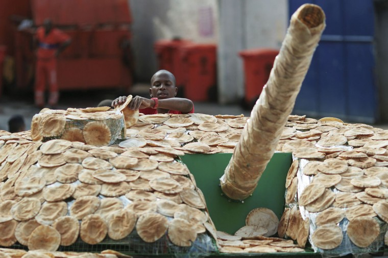 June 19, 2012: A man arranges bread on a life-sized model of a tank at Morro Santa Marta, the first 'pacified' favela, ahead of the Rio+20 conference in Rio de Janeiro. Brazil. The installation by the World Future Council organization symbolizes the use of military expenses to fund social needs and calls for the governments taking part in the Rio+20 conference to work towards disarmament for sustainable development. (Ueslei Marcelino/Reuters)