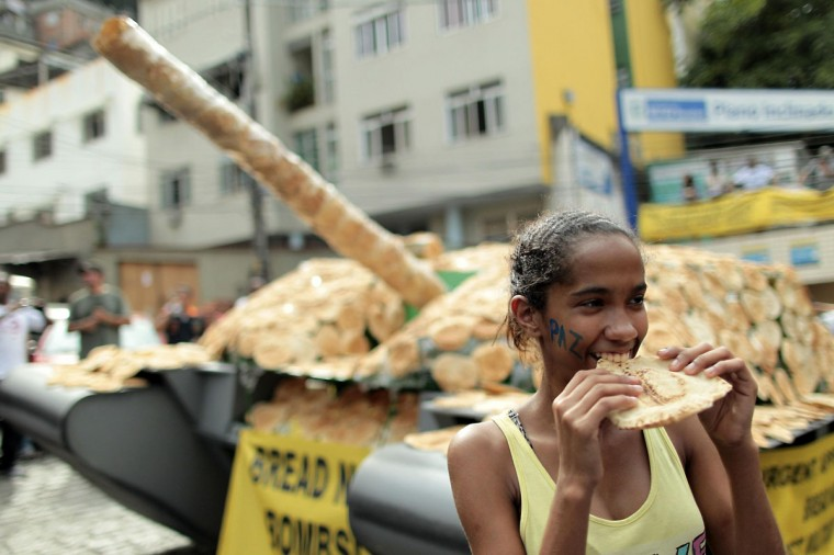 June 19, 2012: A girl eats bread in front of a life-sized model of a tank covered with bread on display at Morro Santa Marta, the first 'pacified' favela, ahead of the Rio+20 conference in Rio de Janeiro, Brazil. The installation by the World Future Council organization symbolizes the use of military expenses to fund social needs and calls for the governments taking part in the Rio+20 conference to work towards disarmament for sustainable development. (Ueslei Marcelino/Reuters)