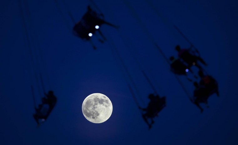 "People ride the Luna Park Swing Ride as the ""supermoon"" rises on Coney Island, June 22, 2013. The largest full moon of the year called the ""supermoon"" will light up the night sky this weekend. (Carlo Allegri/Reuters)"