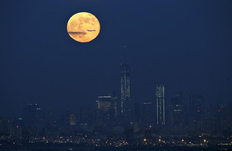 "A full moon also referred to as a ""supermoon"" rises in the sky behind New York's Lower Manhattan and One World Trade Center as a plane passes through it as seen from the Eagle Rock Reservation in West Orange, New Jersey. (Gary Hershorn/Reuters photo)"