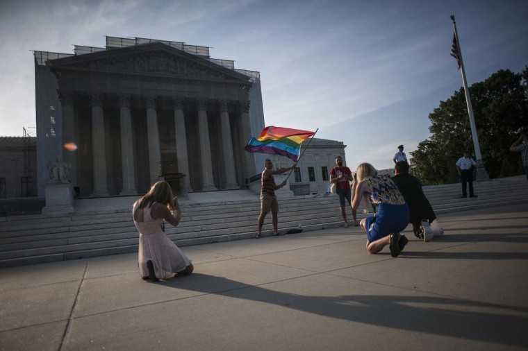 A demonstrator waves a flag while awaiting decisions in two cases regarding same-sex marriage at the U.S. Supreme Court in Washington, June 26, 2013. (James Lawler Duggan/Reuters)