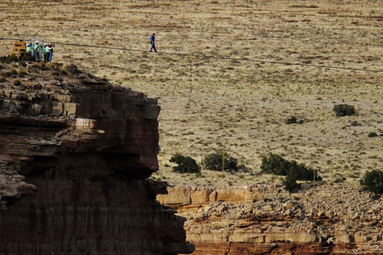 Daredevil Nik Wallenda walks on a two-inch (5-cm) diameter steel cable rigged 1,400 feet (426.7 metres) across more than a quarter-mile deep remote section of the Grand Canyon near Little Colorado River, Arizona June 23, 2013. (Mike Blake/Reuters)