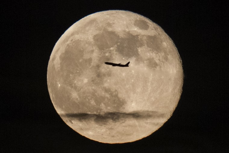 A silhouetted airplane flies past a 'supermoon' over New York. (Zoran Milich/Reuters photo)