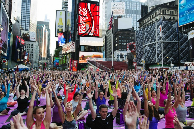 "People take part in a group yoga practice on the morning of the summer solstice in New York's Times Square. The ""Solstice in Times Square"" event on Friday brought out thousands of participants to celebrate the year's longest day in New York. (Lucas Jackson/Reuters)"