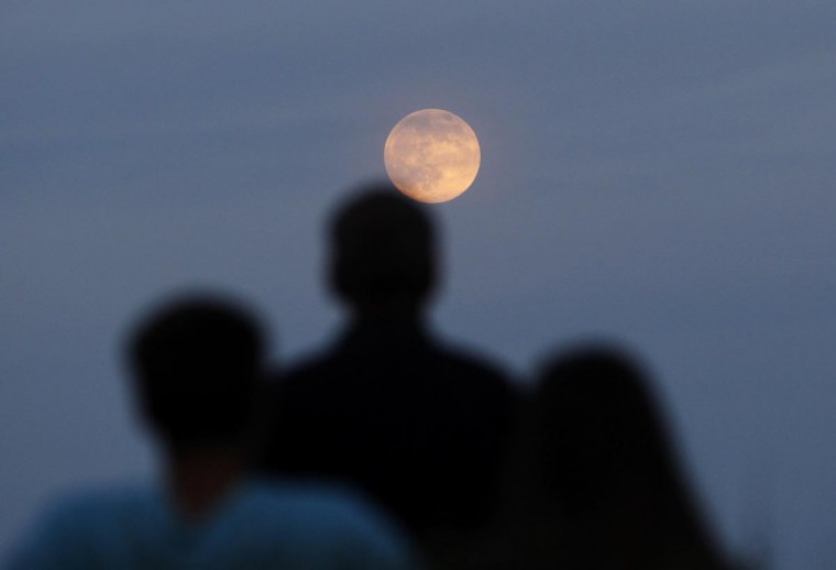 "People watch the full moon also referred to as a ""supermoon"" rise in the sky from the Eagle Rock Reservation in West Orange, New Jersey, June 22, 2013. (Gary Hershorn/Reuters)"
