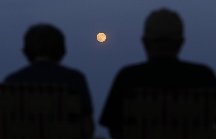 "Two people watch the full moon also referred to as a ""supermoon"" rise in the sky from the Eagle Rock Reservation in West Orange, New Jersey, June 22, 2013. (Gary Hershorn/Reuters)"