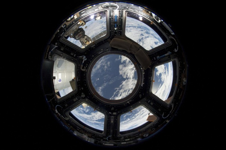 A view of Earth from the Cupola on the earth-facing side of the International Space Station is seen in this NASA handout photo taken June 12, 2103 and provided June 17, 2013. Visible in the top left foreground is a Russian Soyuz crew capsule. In the lower right corner, a solar array panel can be seen. (NASA handout via Reuters)