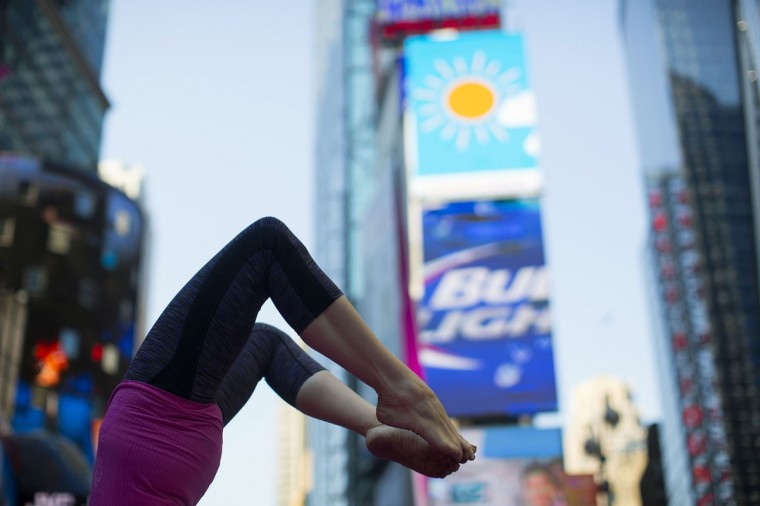 """A woman takes part in a group yoga practice at the """"Solstice in Times Square"""" event in New York's Times Square on the morning of the summer solstice, June 21, 2013. (Eric Thayer/Reuters)"""
