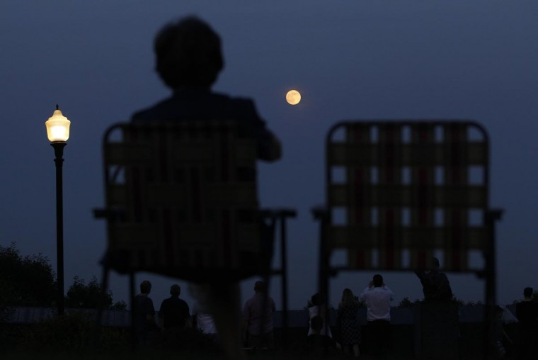 "A woman watches the ""supermoon"" as it rises in the sky from the Eagle Rock Reservation in West Orange, New Jersey, June 22, 2013. (Gary Hershorn/Reuters)"
