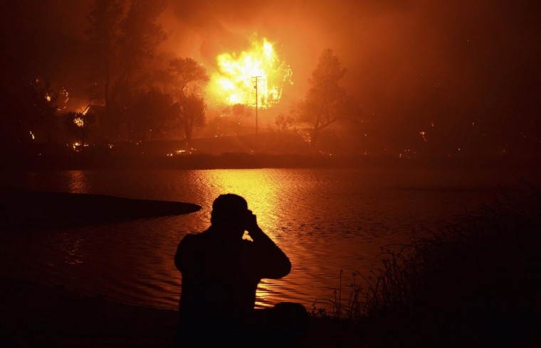 A local resident looks at a neighbor's two-story house engulfed in flames, as firefighters battle the Powerhouse wildfire at the Angeles National Forest, with the fire now having destroyed several homes near the Lake Hughes area in California June 1, 2013. The Powerhouse Fire remained at 15 percent containment after ravaging over 5,600 acres of the forest by Saturday evening. (Gene Blevins/Reuters)