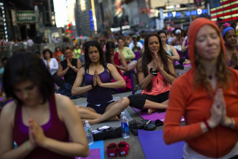"""People take part in a group yoga practice at the """"Solstice in Times Square"""" event in New York's Times Square on the morning of the summer solstice, June 21, 2013. (Eric Thayer/Reuters)"""
