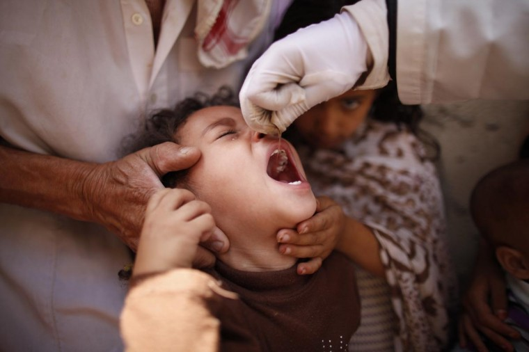 A child receives an oral polio vaccine during an anti-polio campaign in Sanaa June 30, 2013. (Khaled Abdullah/Reuters)