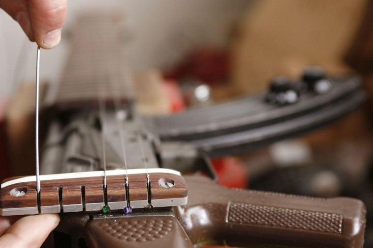 October 2, 2006: Colombian instrument maker Jose Paredes assembles an AK47 rifle to be converted to an electric guitar in his workshop in Bogota, Colombia. A top musical craftsman, Luis Alberto Paredes and his family have branched out from their fine classic string instruments to fashion electric guitars from shotguns and AK47s once used by fighters caught up in the country's lingering conflict. (Jose Miguel Gomez/Reuters)