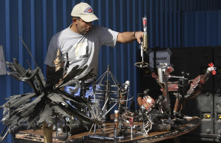 December 30, 2008: A member of the Iraqi Mine/Unexploded Ordnance (UXO) Clearance Organization displays metal sculptures made from destroyed weapons in Baghdad. Some of the destroyed weapons confiscated by the U.S. military from raids and search operations are made into different kinds of artistic metal sculptures. (May Naji/Reuters)